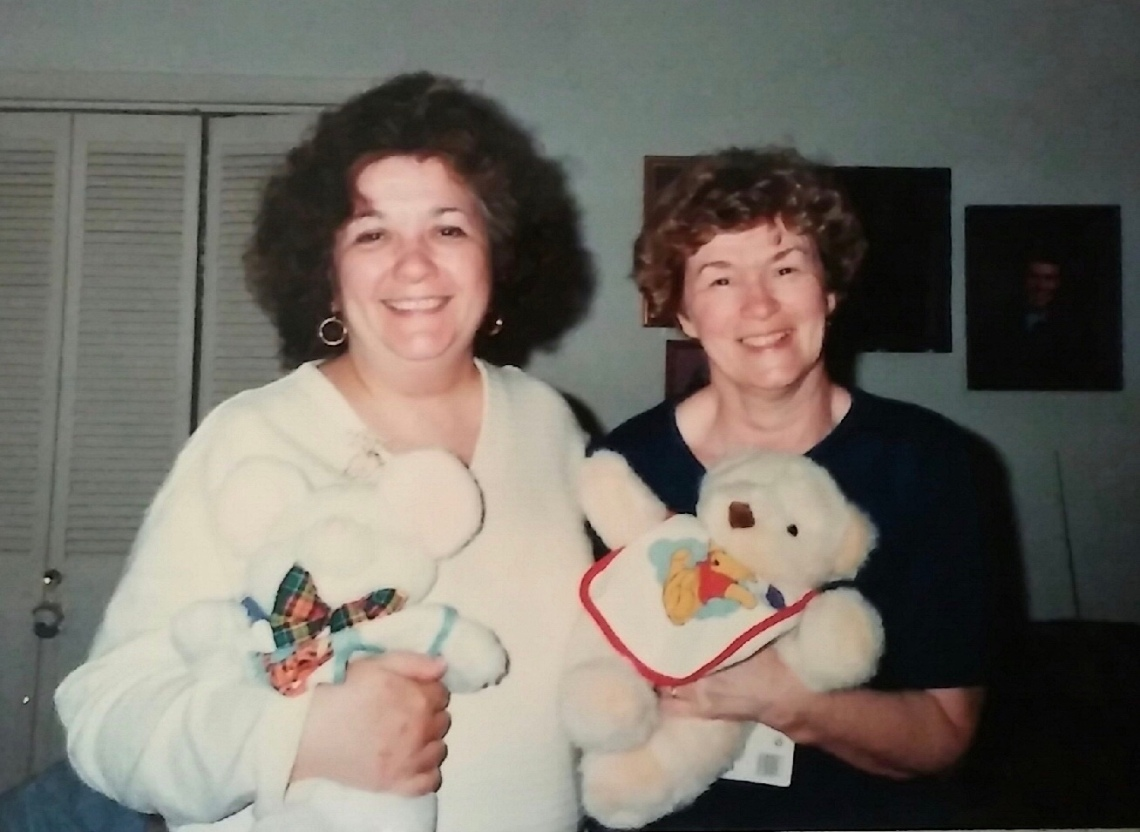 Picture of my grandmothers smiling, holding teddy bears with bibs on them.